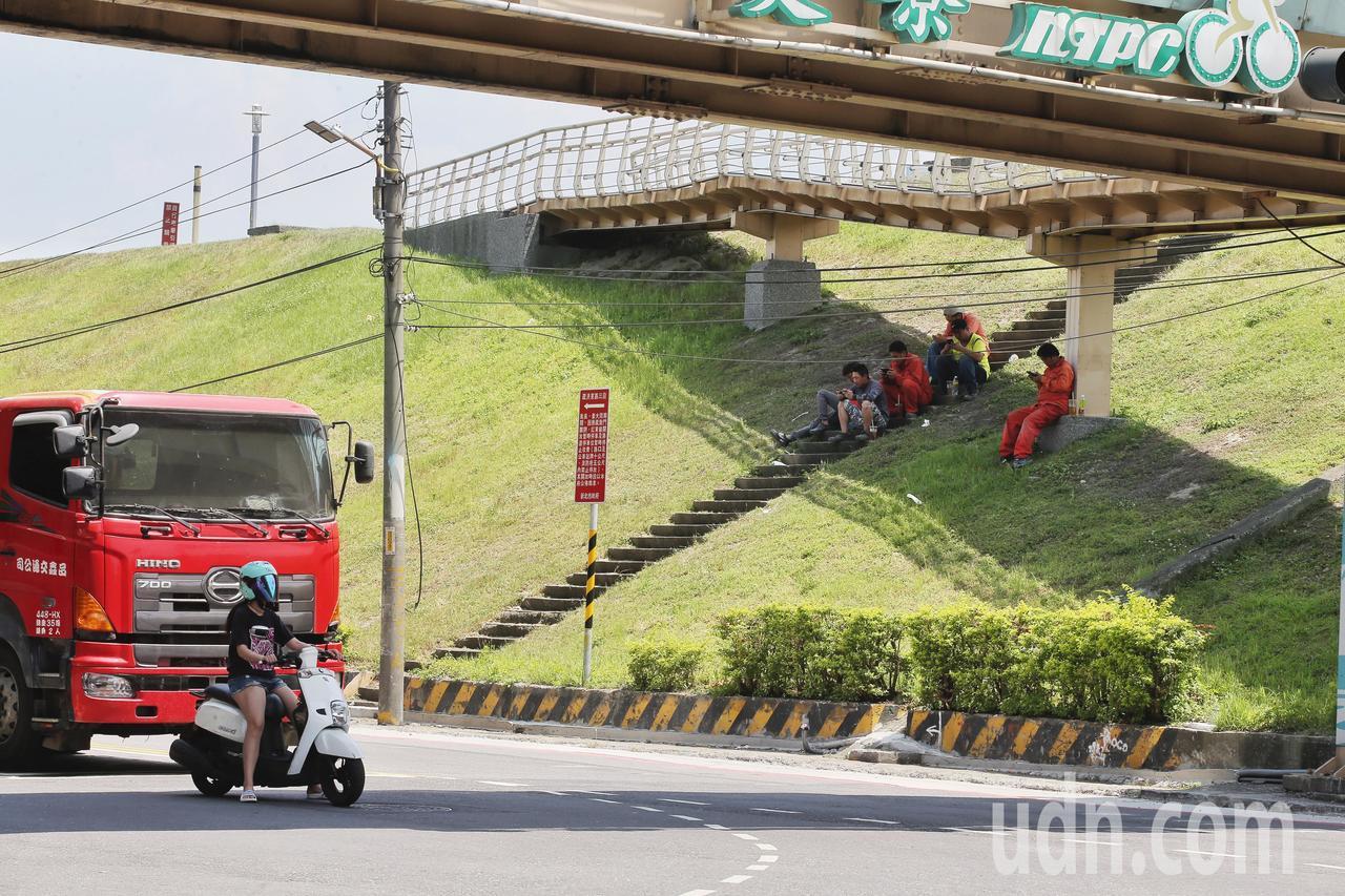 中午休息的工人在橋下休息,與躲在橋下的機車騎士。記者楊萬雲/攝影
