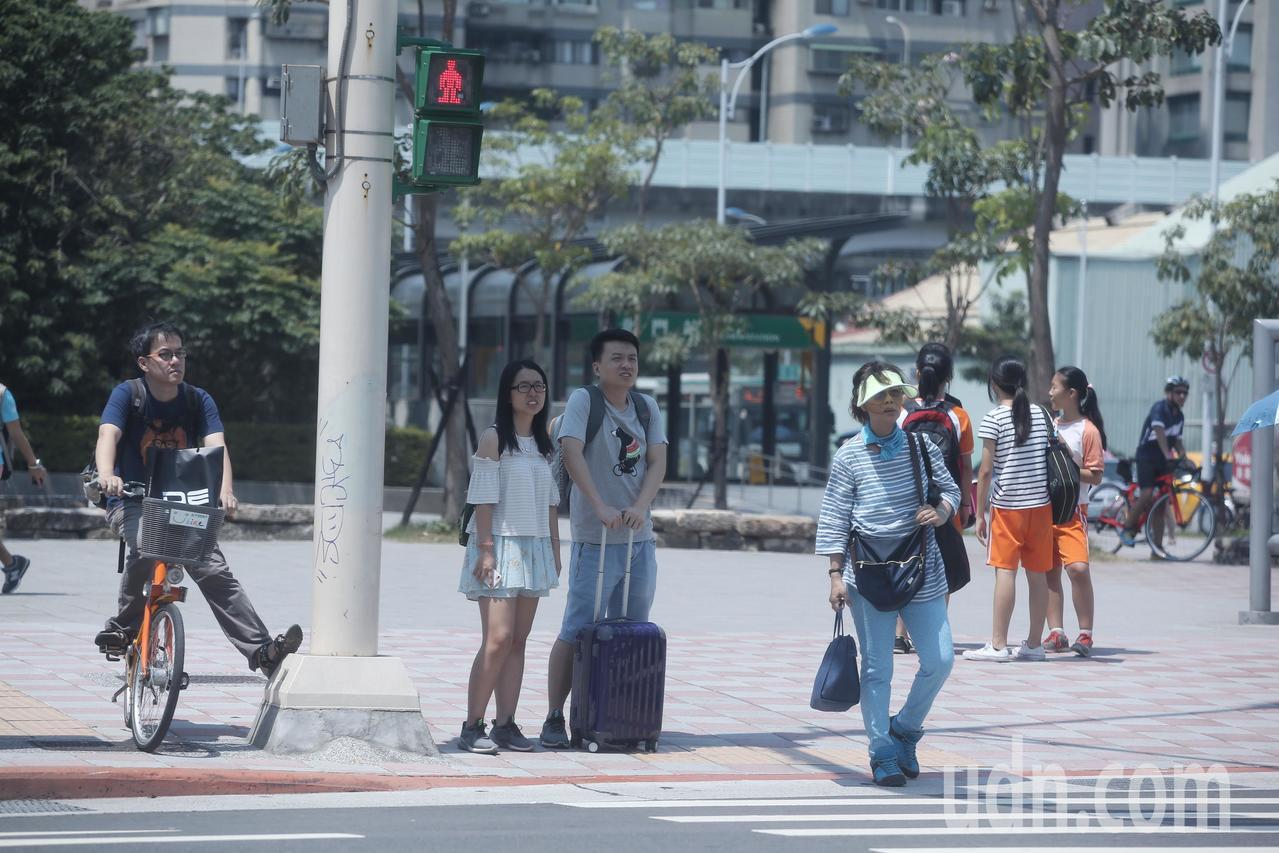 行人過馬路時,躲在路燈下等紅燈。記者楊萬雲/攝影