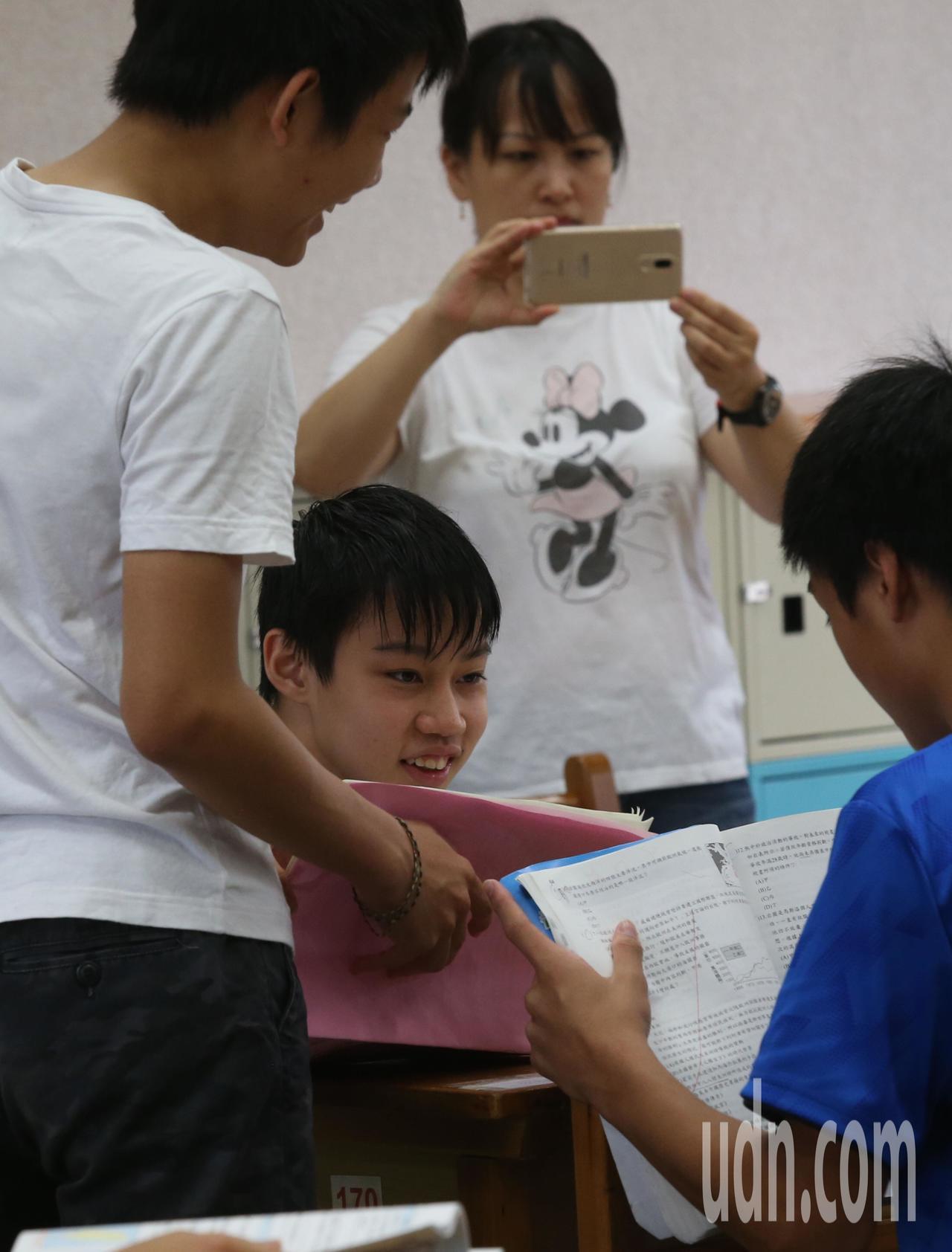 國中教育會考今天登場,一早考生在家長陪同下,進入考場準備應試,並不忘拍照留念。記...