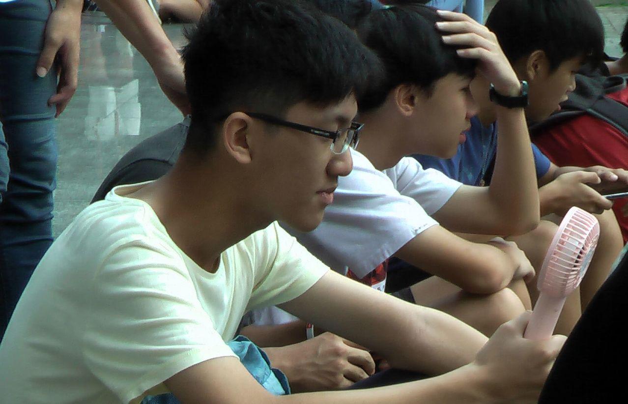 高雄今天高溫炎熱,考生拿著小電風扇猛吹。記者徐如宜/攝影