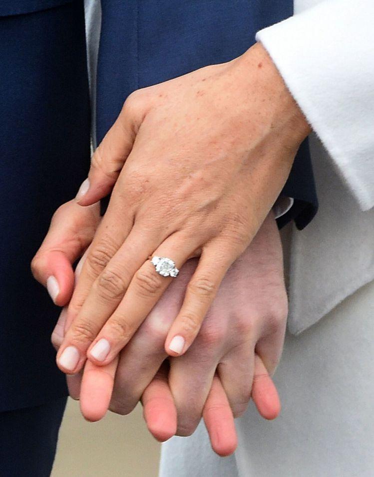 梅根的訂婚戒指由哈利王子親手設計,主鑽旁的兩顆鑽石取自黛安娜王妃擁有的珠寶,象徵...