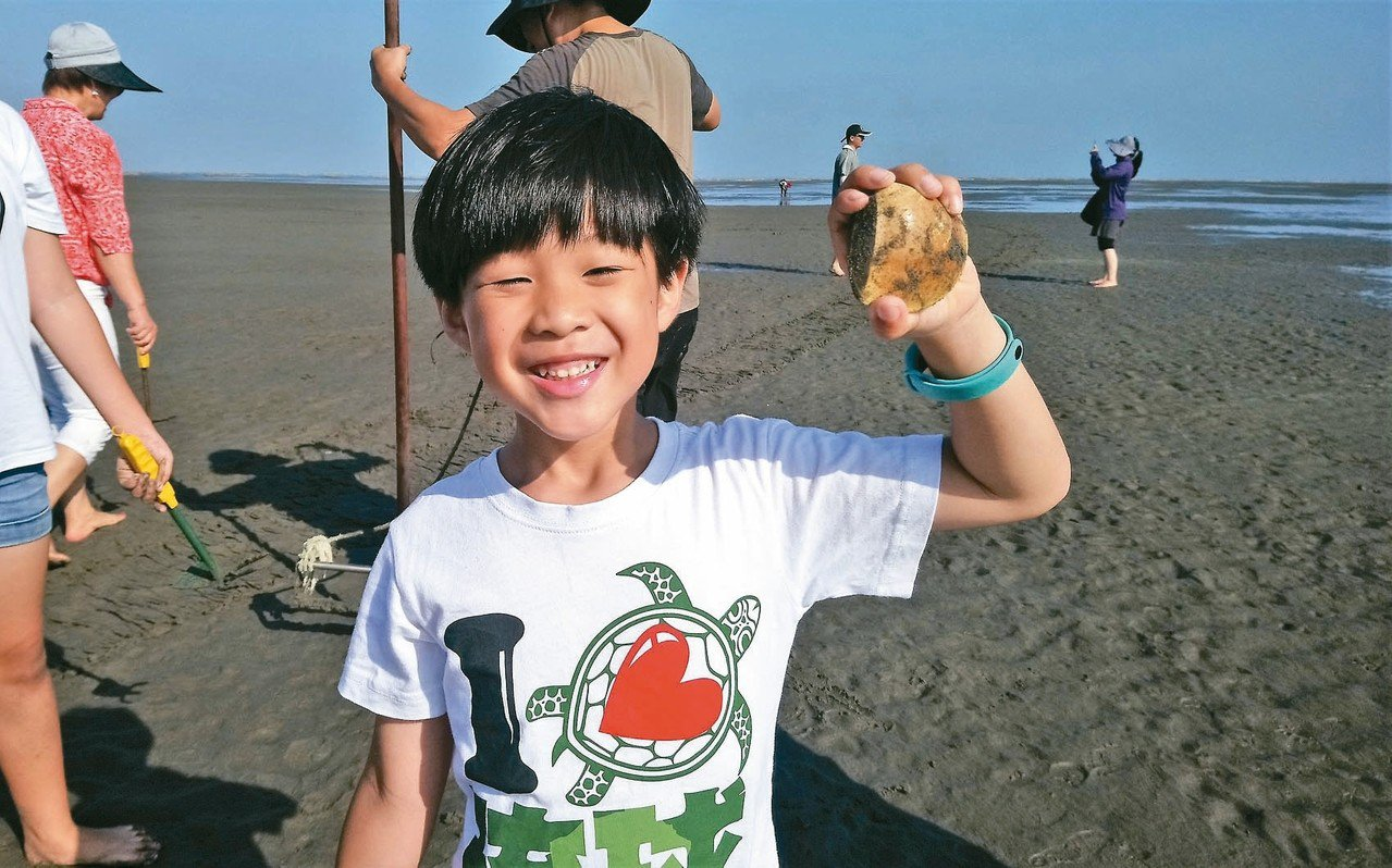 小朋友開心展示登洲挖到的野生大文蛤,幾乎如手掌般大。 記者卜敏正/攝影
