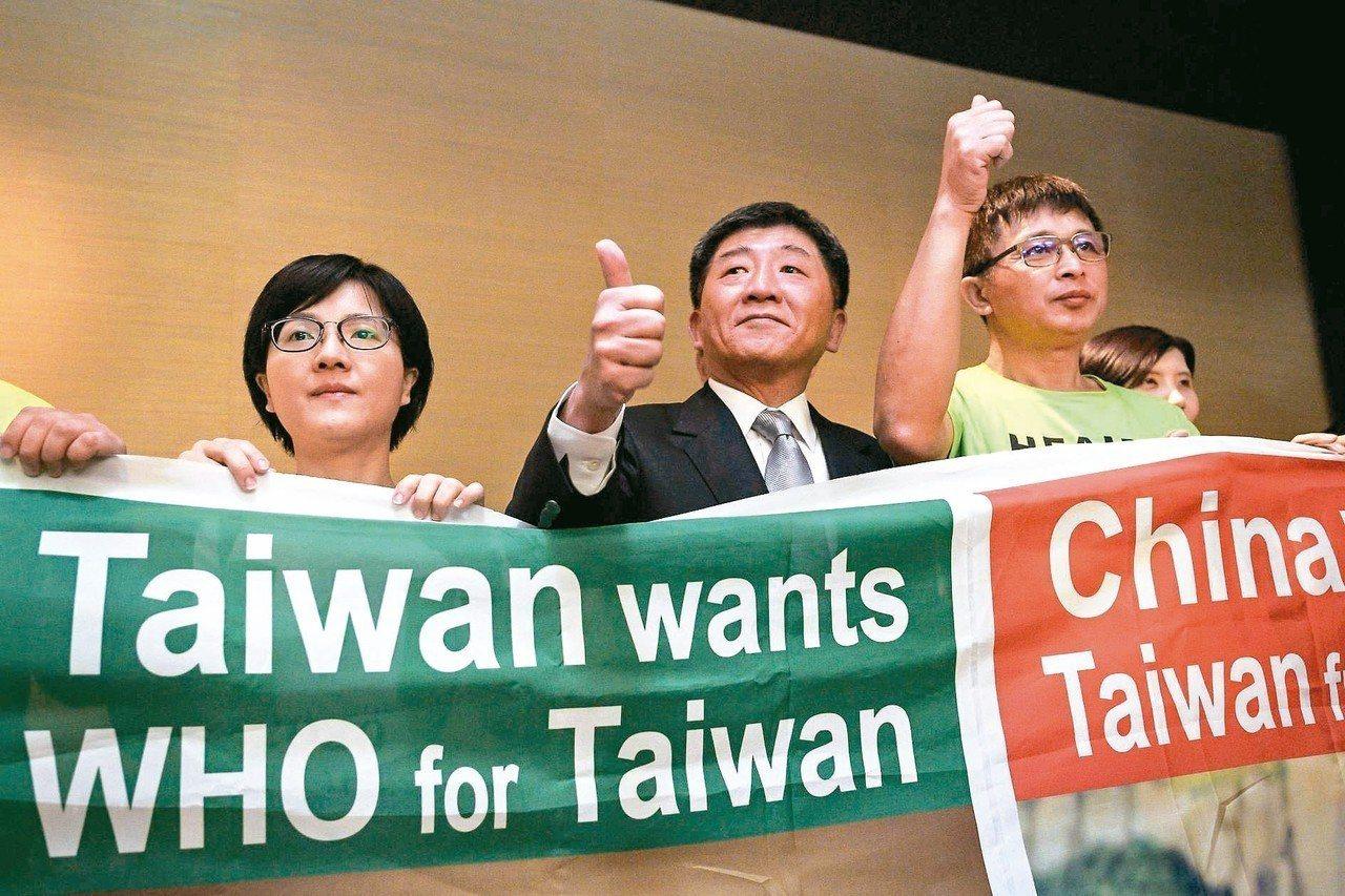 衛福部長陳時中(中)廿一日在瑞士日內瓦舉行國際記者會後,豎起拇指與示威者一起舉起...
