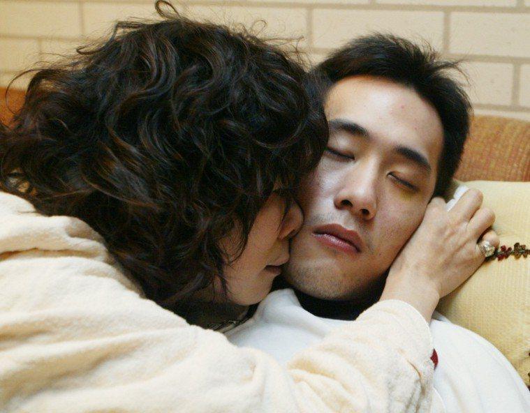 2005年余祥銓(右)身心崩潰,李亞萍不捨抱著他。報系資料照