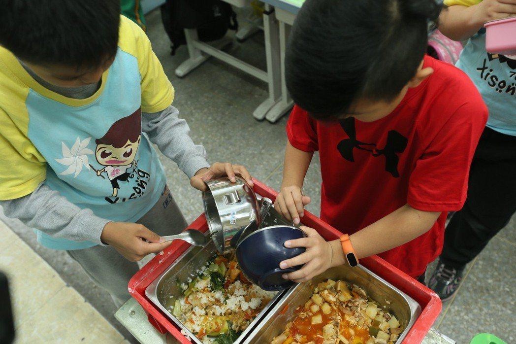學生將沒吃完的營養午餐倒入餐盒中。記者林伯東/攝影