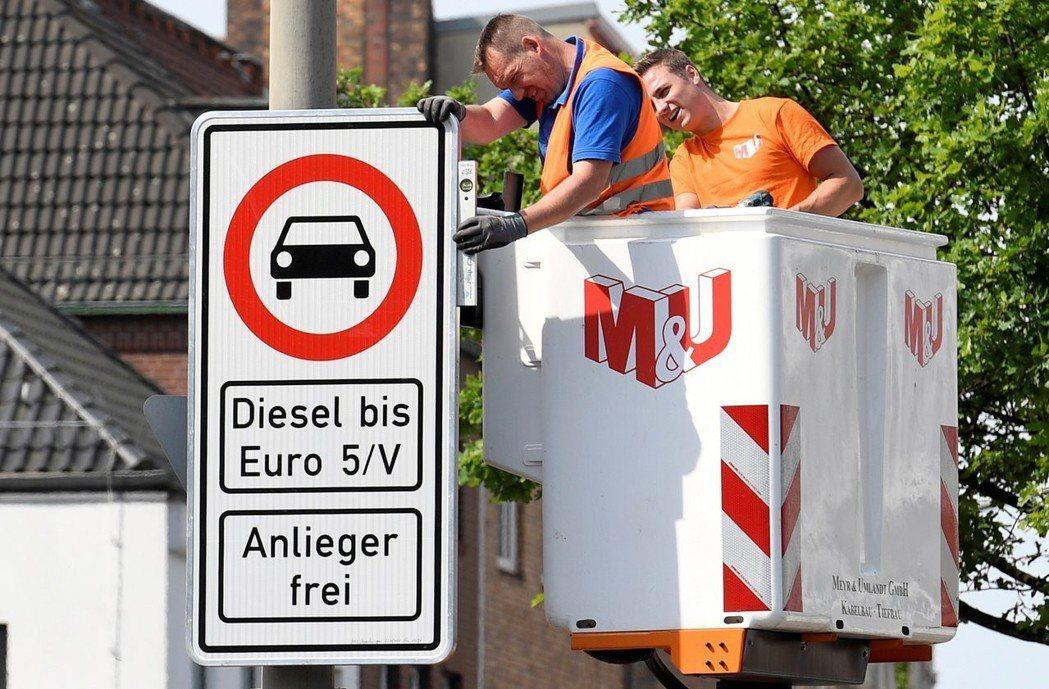 兩名工人正在漢堡市區裝設禁行柴油車告示牌。漢堡兩條主要幹道將在31日起禁止較舊的...