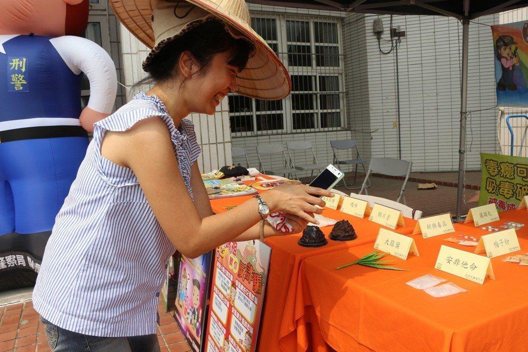 雲林國中老師前往毒品展示攤位拍攝,用來做與學生講解教材。記者邱奕能/攝影