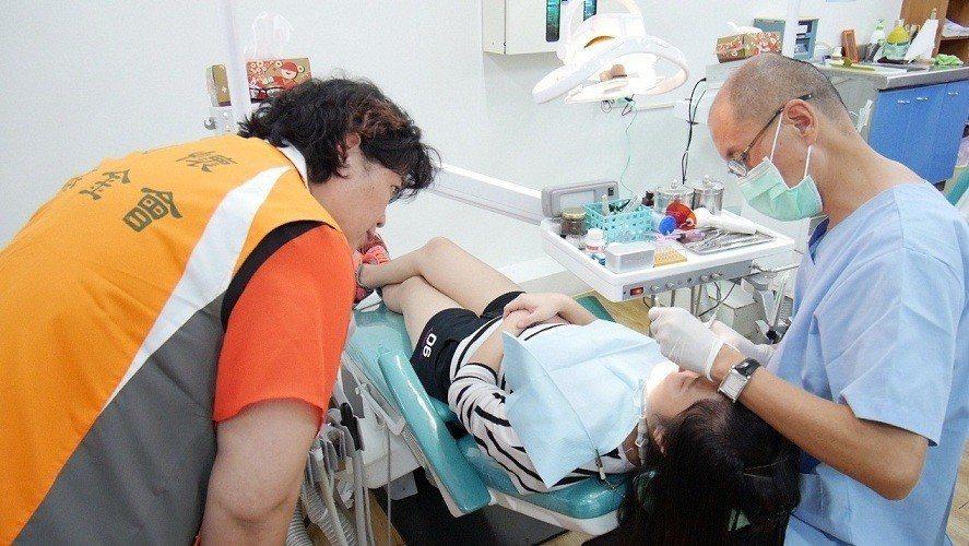 慈懷基金會的生活輔導阿姨帶著孩子就醫看牙齒。圖由慈懷基金會提供。