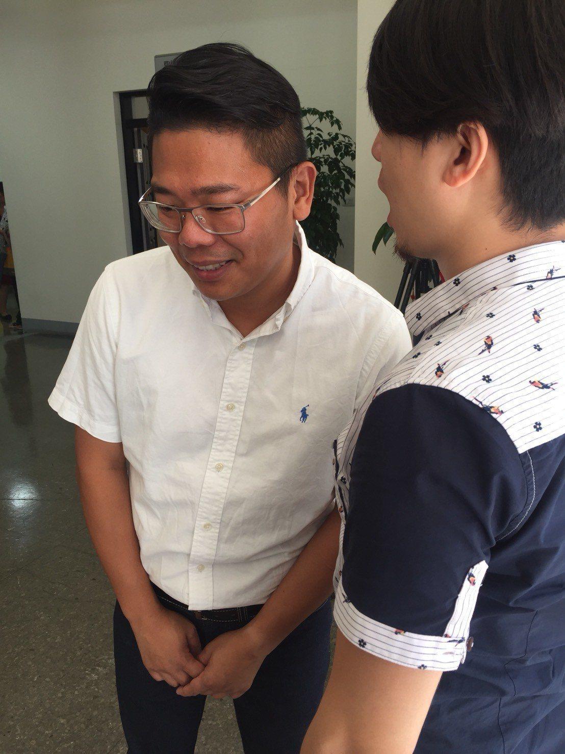 新竹市議員林盈徹(左)因從小聽力受損、配戴電子耳,與人對話時很專注聆聽。記者郭宣...