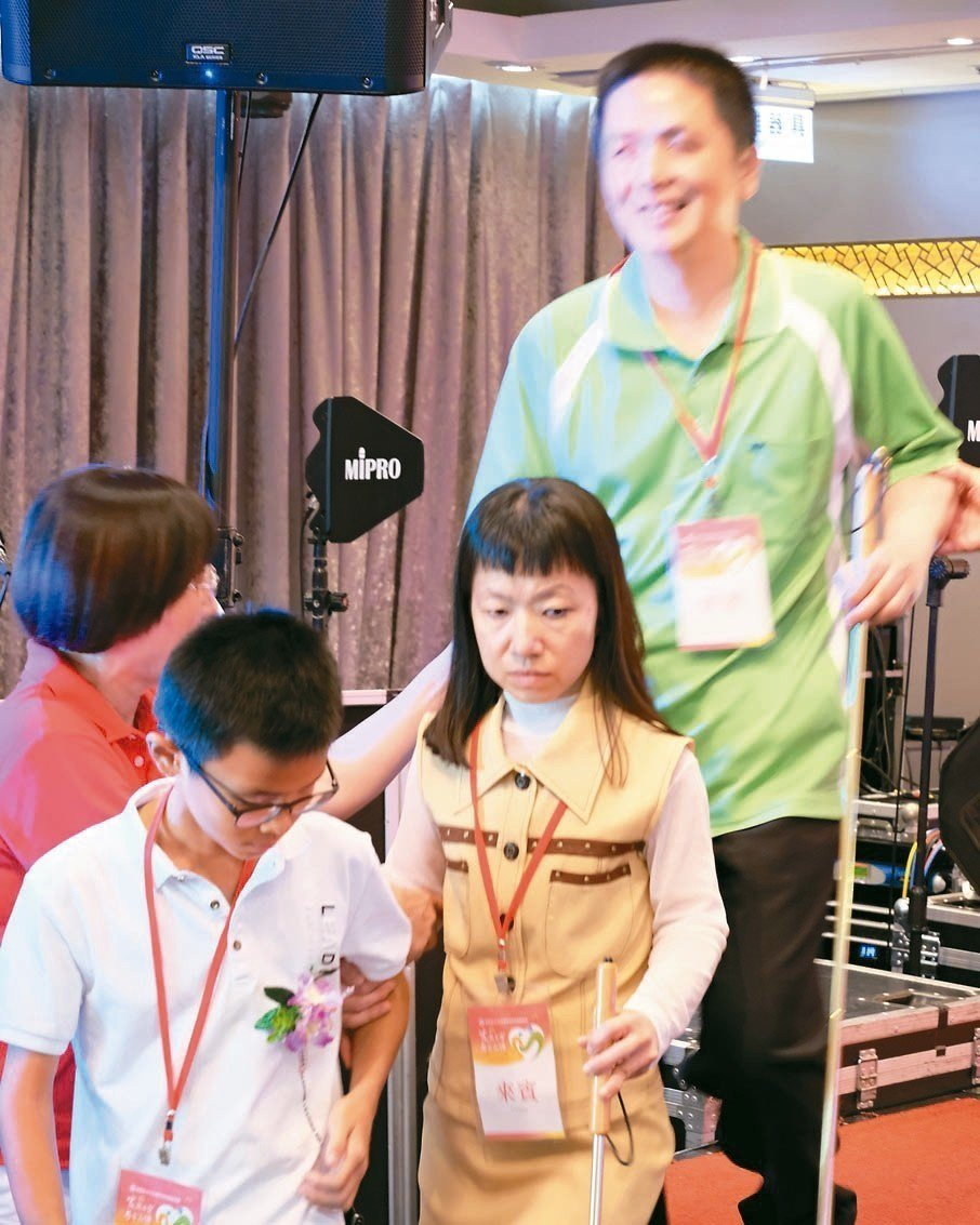 獲獎的陳韋仁(左)挽著母親的手,父親再把手搭在母親肩上,他當起雙親的眼睛引導他們...