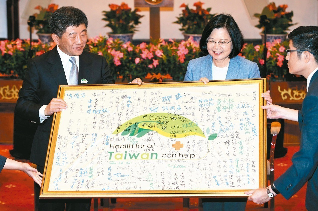 蔡英文總統上午接見「世衛行動團」,衛福部長陳時中(左)把代表團簽名的旗幟送給蔡總...