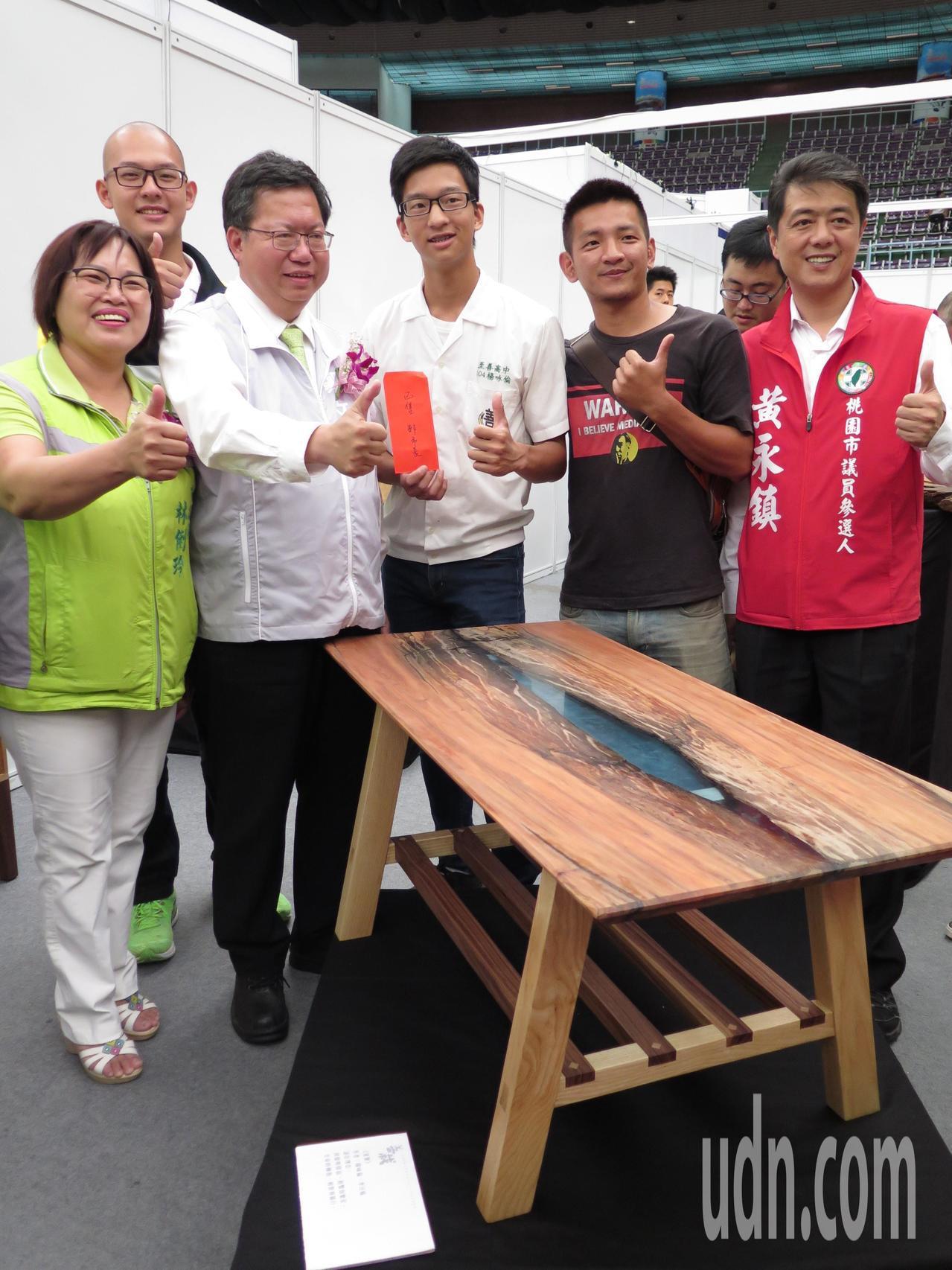 市長鄭文燦(左三)今天到桃園木創與家居生活展,看見高三生親手打造的方形木桌,自掏...