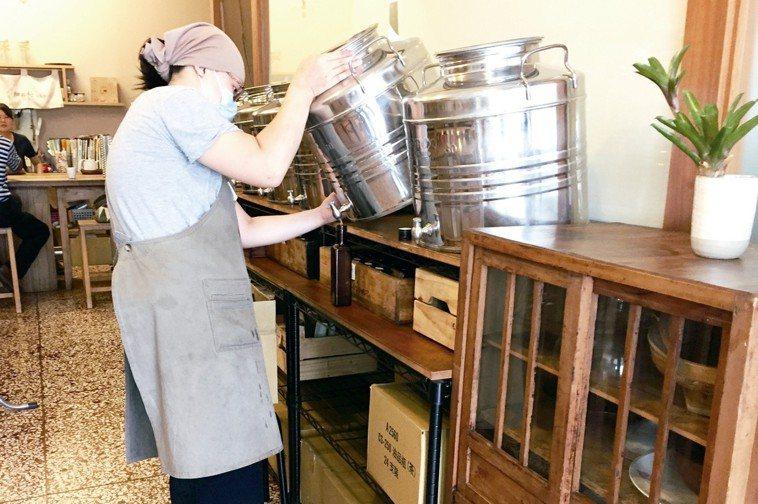 「細粒籽油工房」內,擺放著一列不鏽鋼桶裝的現榨油。 朱慧芳
