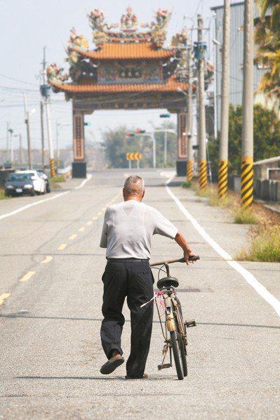 嘉義東石洲仔村民楊水利,牽著破舊單車當拐杖,走到距離1.1公里的村外站牌等公車。...