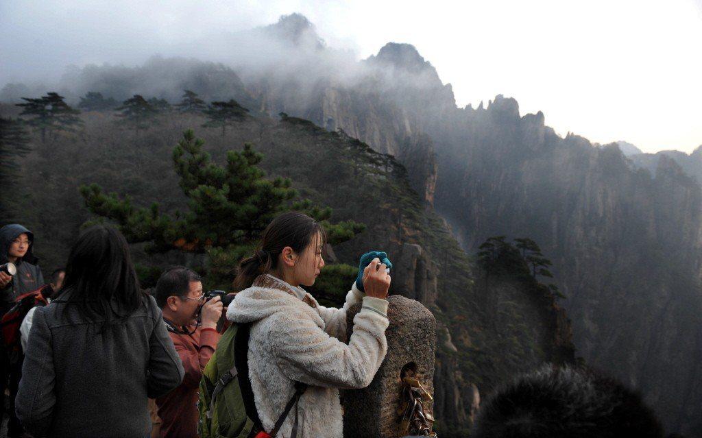 黃山歸來不見岳,被籲為全中國最美的山。圖為遊客飽覽黃山風光。(新華社)