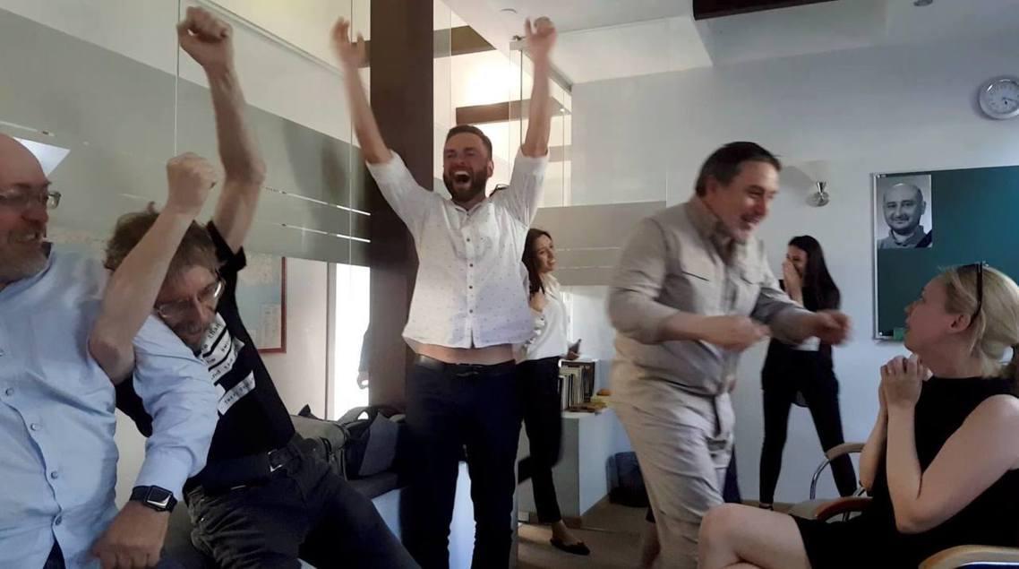 記者同事們看到巴布琴科還活著,歡喜大驚呼。右上角還可見辦公室掛上巴布琴科的遺像。...