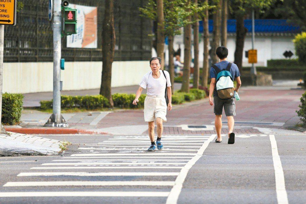 為減少行人魂喪馬路虎口,交通部允諾研究「兩段式行人穿越道」。圖為台北市民眾過馬路...