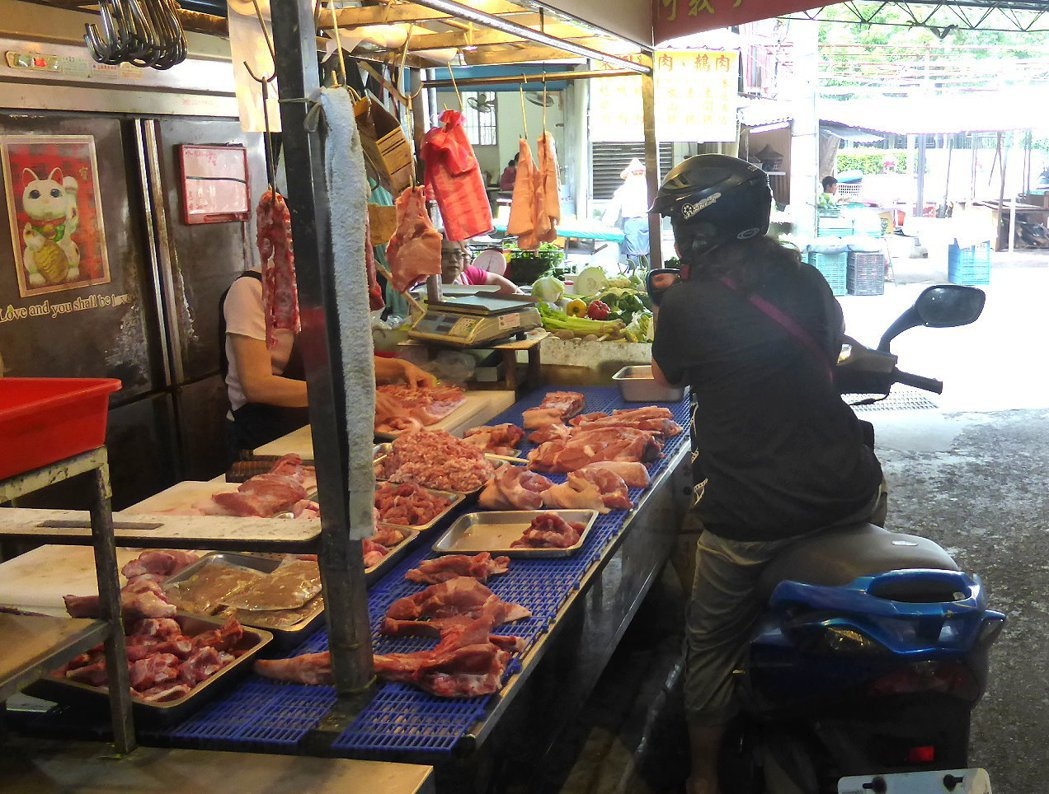 許多婆婆媽媽習慣直接騎機車進市場買菜,卻疏忽了機車排氣管可能燙傷路人。 記者王宏...