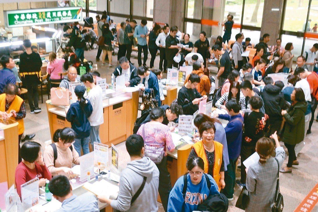 領務大廳一樓申辦護照人潮多,現場志工穿梭,協助民眾填表及引導。 領事事務局╱提供
