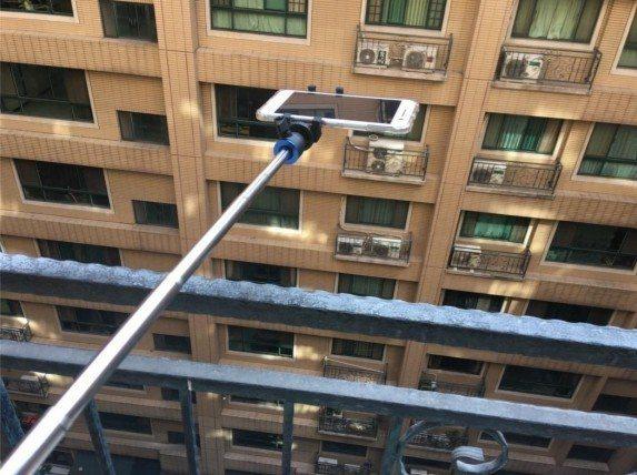 鑑識人員使用藍芽自拍棒,讓手機可拍到窗戶外狀況。 記者袁志豪/翻攝
