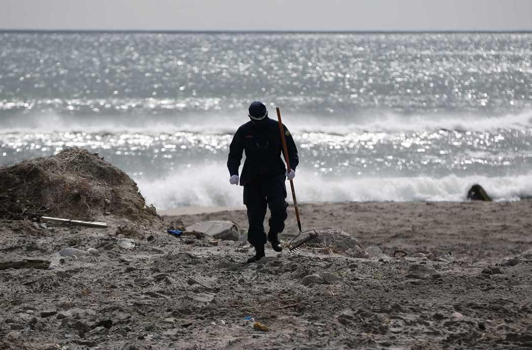 搜救人員持續在浪江町海岸線搜尋失踪者,攝於2014年3月11日。 圖/路透社