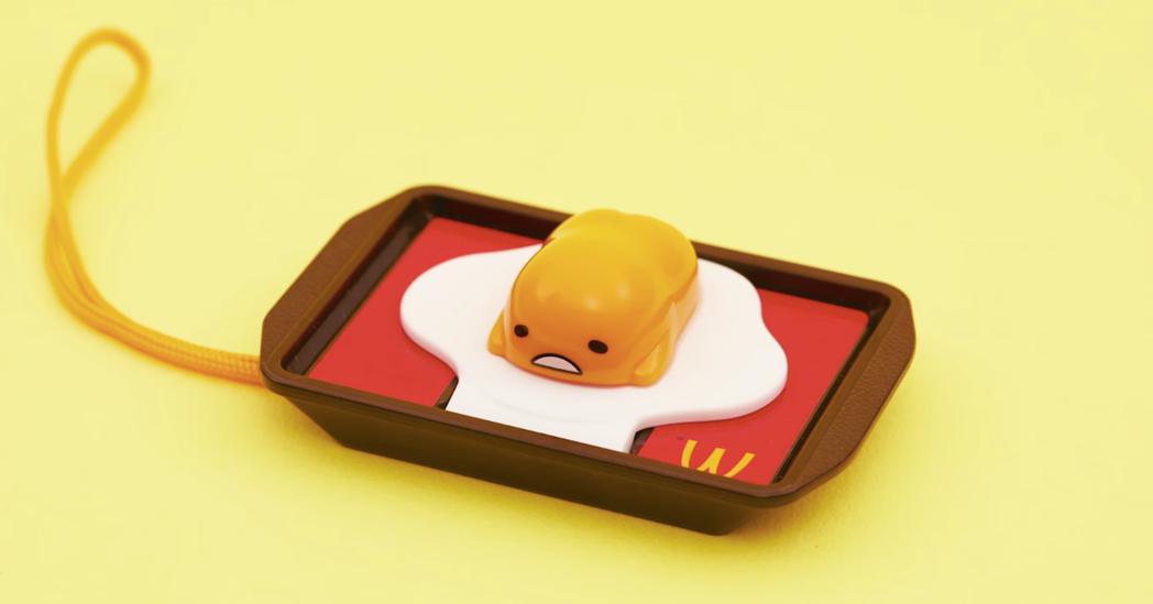 日本麥當勞攜手蛋黃哥推出兒童餐玩具系列,蛋黃哥趴在餐盤上也很療癒。圖/摘自日本麥...
