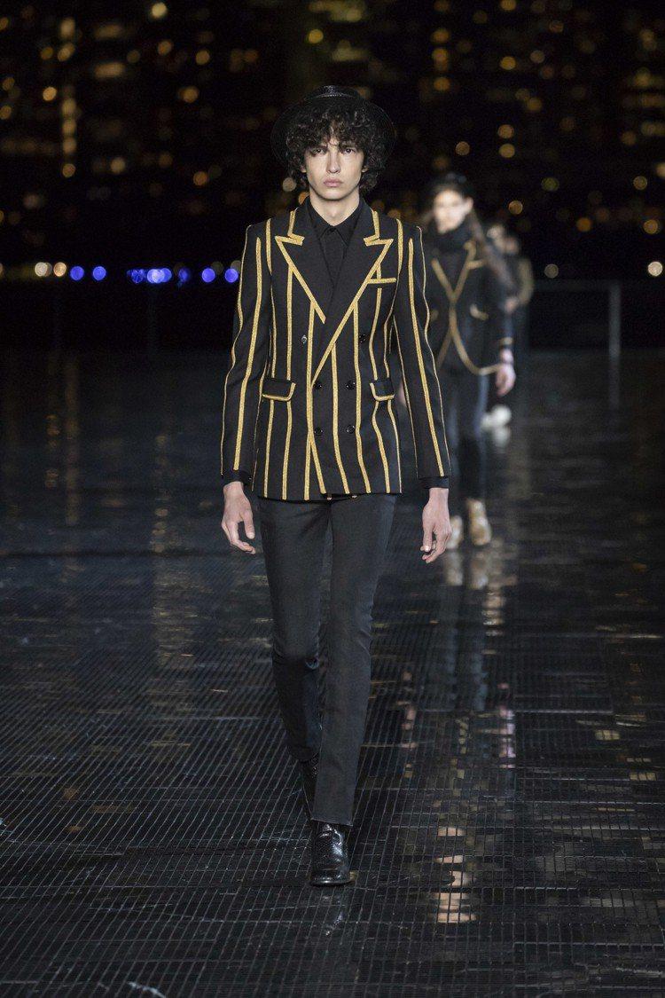 男模們身穿品牌標誌性暗黑風格窄版服飾現身,閃閃發光的金黃色元素點綴細節,恰巧和夜...