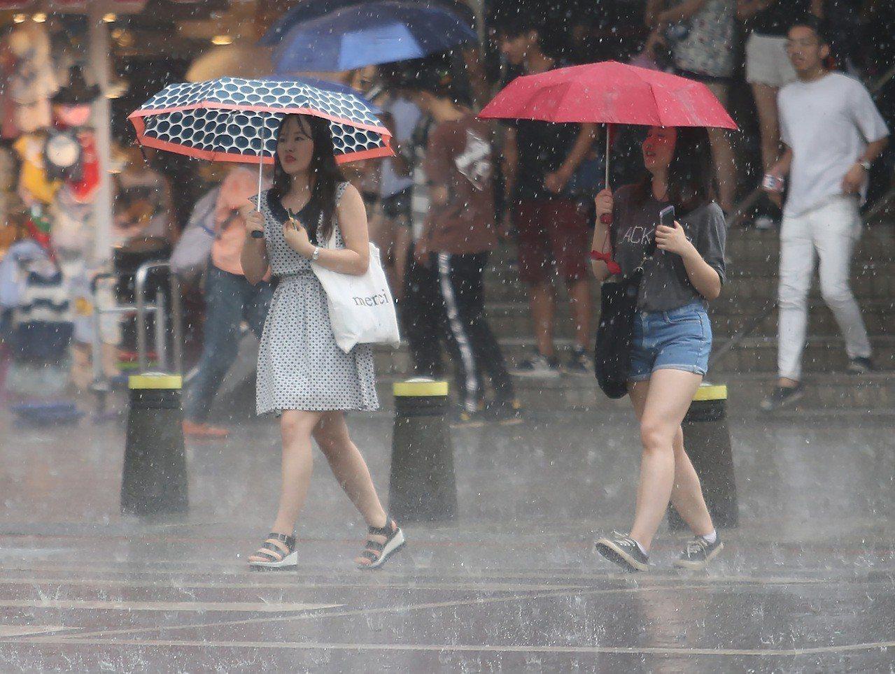 圖為台北午後大雨,民眾撐傘遮擋雨勢過馬路。 中央社