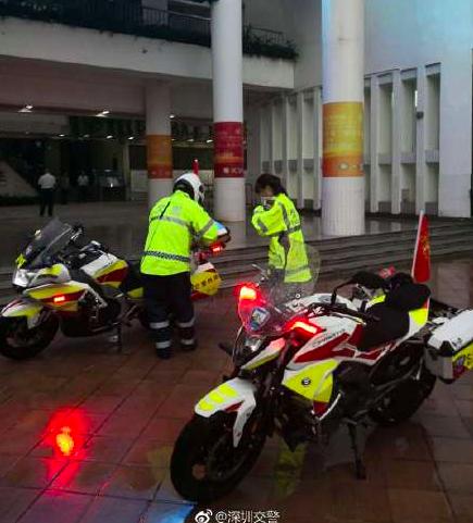 深圳南山交警第二高級中學駐點交警為考生穿好雨具,趕回學校拿准考證,並及時送考生回...