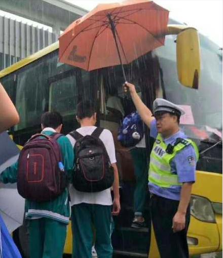 佛山民警在大雨中為考生撐傘擋雨。 圖/摘自微博「公安主持人」