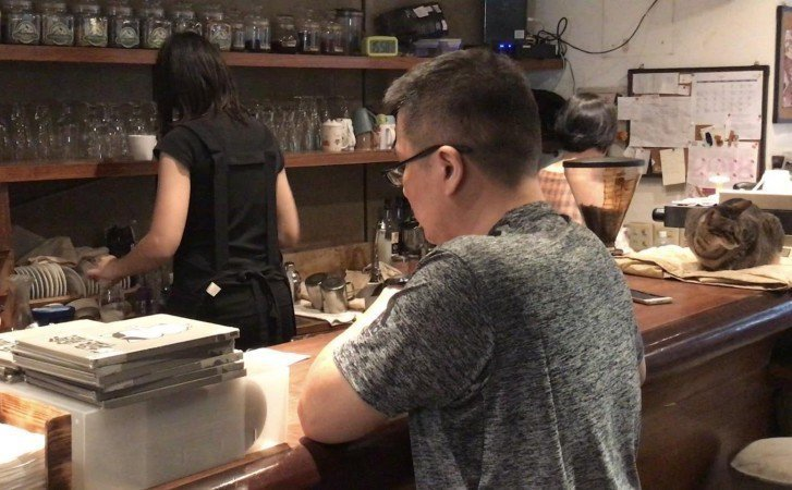 阿寰於極簡咖啡廳寫下餐點的專注樣子。吳欣儒提到,他甚至帶回前輩的手稿,努力學習記...