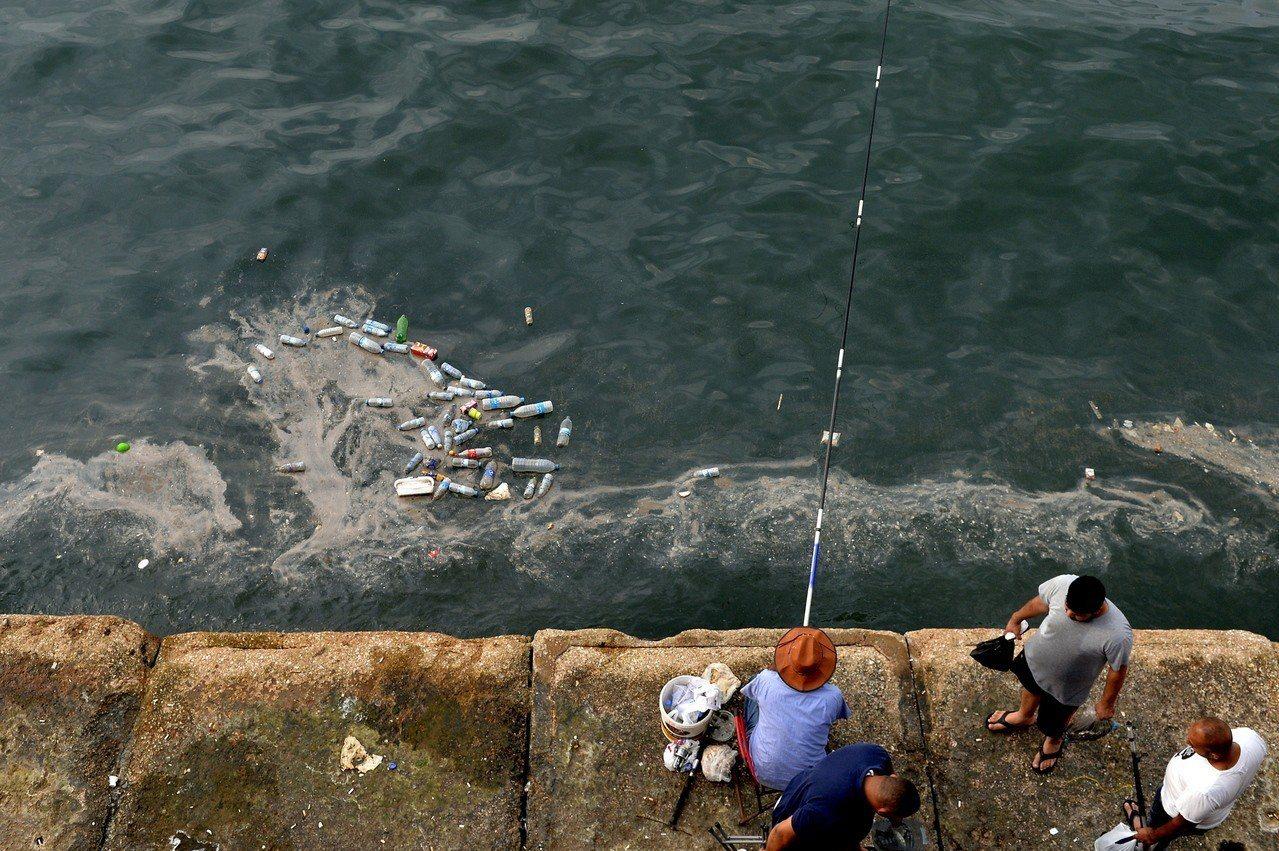 地中海沿岸城市黎巴嫩貝魯特的居民釣魚時,岸邊飄浮許多塑膠瓶和垃圾。歐新社