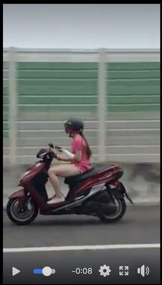 台中市一名穿著熱褲的女騎士今天被網友拍到,騎車上國道一號,還邊騎車邊用手機。圖/...