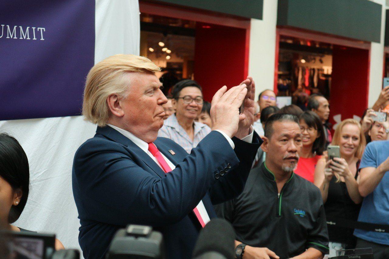 山寨版川金會今天在新加坡洲際飯店先登場,現場擠滿圍觀民眾拍個不停,「川普」也拿起...