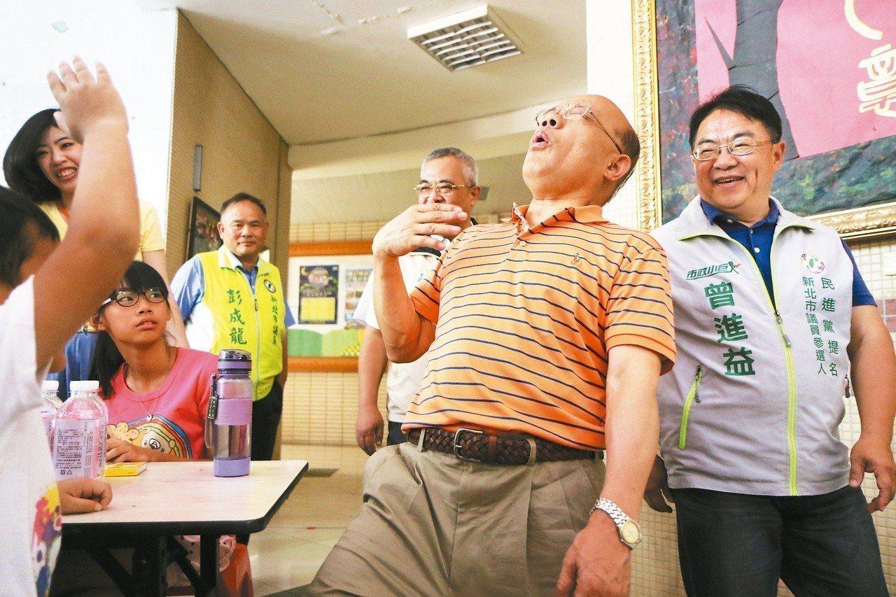 民進黨新北市長參選人蘇貞昌和小朋友們擊掌時,對方擊掌力道稍微大一點,他還會面露痛...