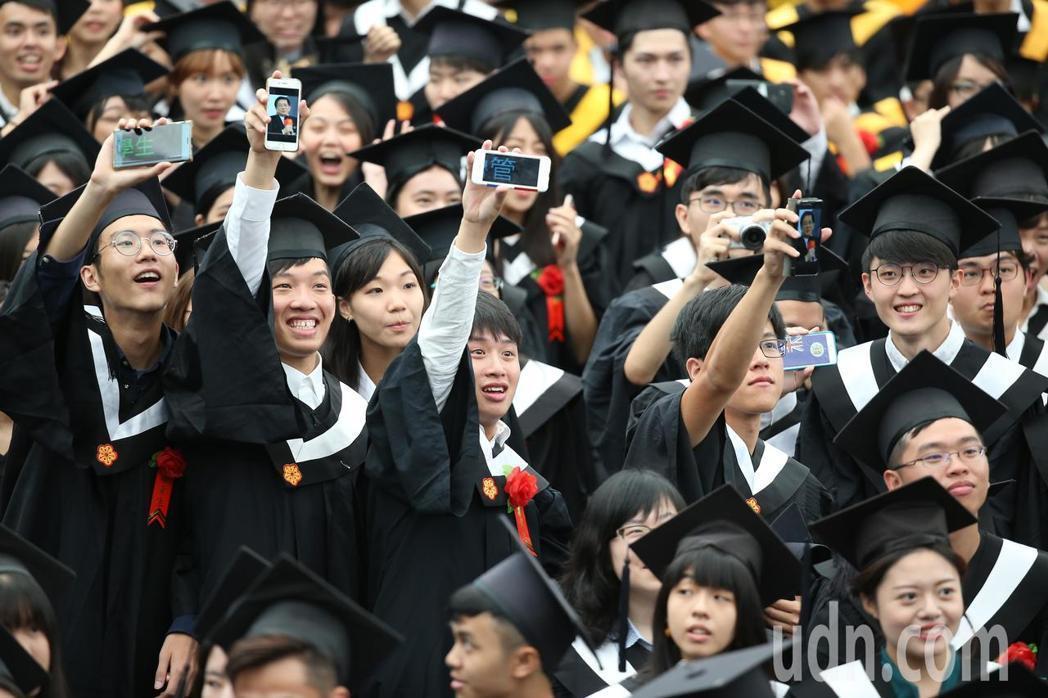 台灣大學畢業典禮,畢業生以手機秀出照片,表達對台大校長風波意見。記者余承翰/攝影