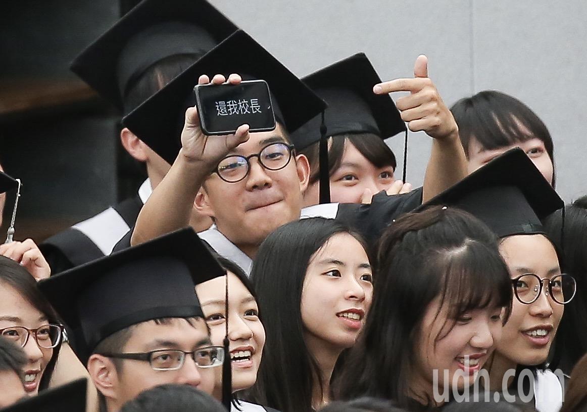 台灣大學畢業典禮,畢業生以手機秀出「還我校長」。記者余承翰/攝影
