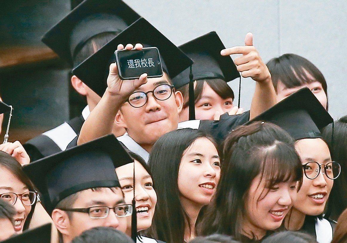 台大畢業典禮由代理校長郭大維代表頒發畢業證書,畢業生秀出「還我校長」等字句。 記...