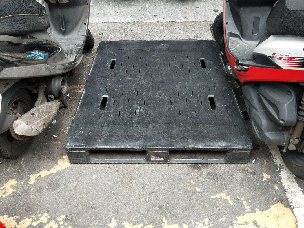 很多商家為了不讓汽機車違停,不少在門口道路範圍放上大塊棧板、塑膠板占位。 記者游...