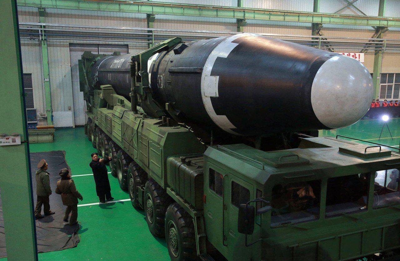 2017年11月,北韓官方對外披露的這張照片顯示,北韓領袖金正恩(左3)站在一枚...