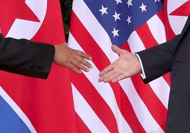 美國總統川普(右)和北韓領導人金正恩握手,背後有六面美國國旗和六面北韓國旗。路透
