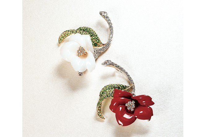 白色茶花為珊瑚,紅色茶花是漆器,綠葉則以沙弗萊石來呈現。並適當選用不同顏色的K金...