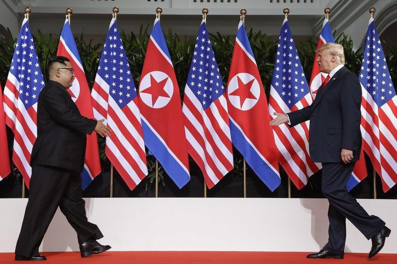 美國總統川普(右)和北韓領導人金正恩12日上午在新加坡首次見面,走向彼此。美聯社
