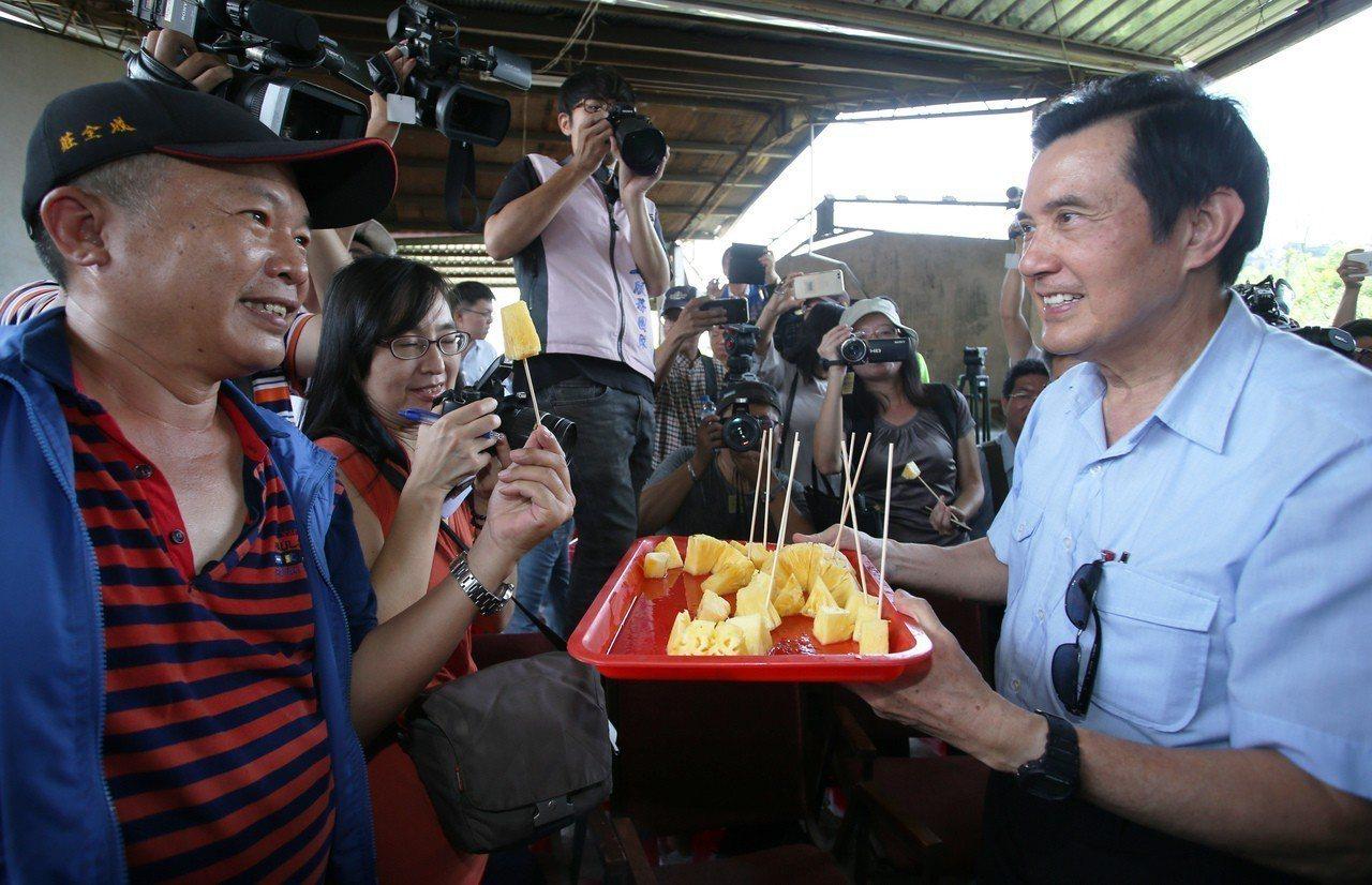 化身鳳梨代言人的馬英九,端起一盤鳳梨請現場民眾享用。記者劉學聖/攝影