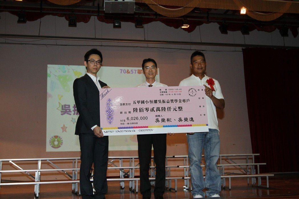 吳健亨(左)代表恒耀企業致贈結婚禮金給母校五甲國小,並由該校校長劉英國(中)代表...