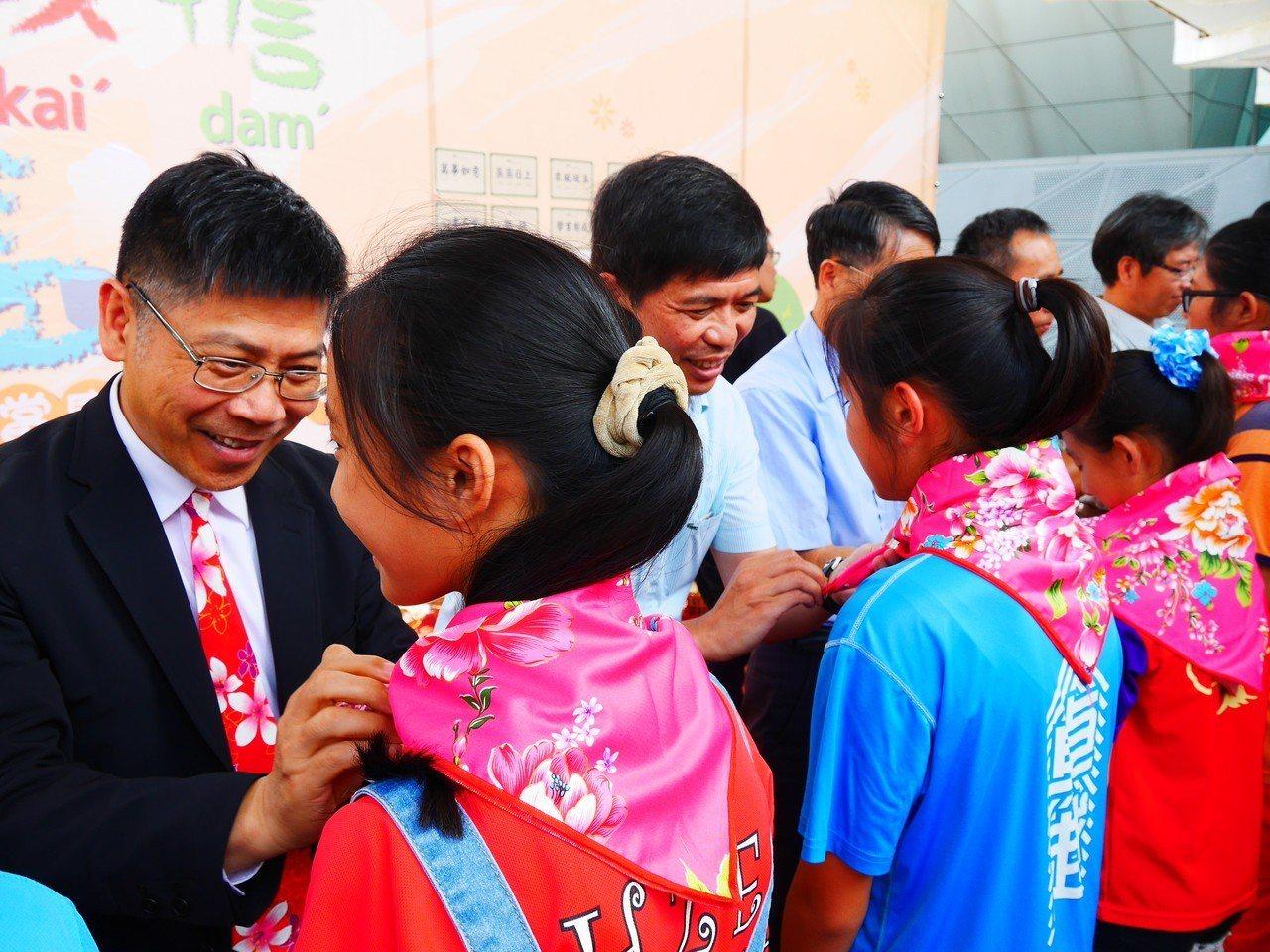 來賓為學童繫上「智慧巾」,勉勵大家用智慧面對人生難題。圖/客家文化發展中心提供