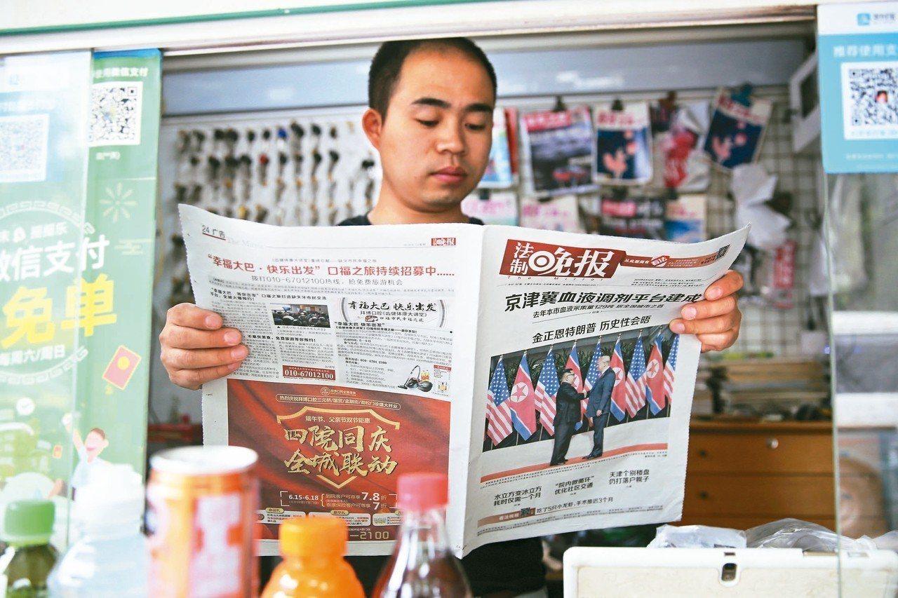 川金會結束,北京一民眾拿著報導峰會的報紙仔細閱讀。 歐新社