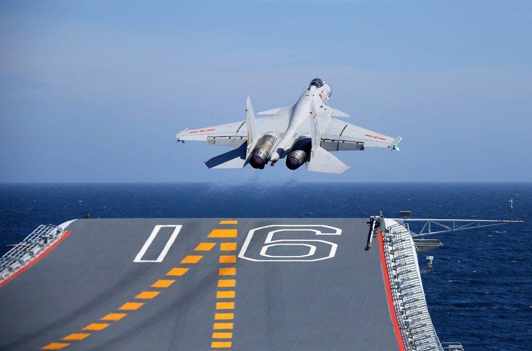 殲-15艦載戰鬥機去年7月,從遼寧艦飛行甲板滑躍起飛。 (中新社)