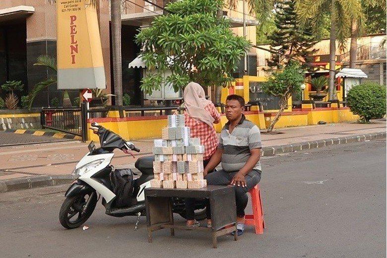 印尼有80%的人沒有銀行帳戶,因應開齋節津貼和現金需求,馬路上也到處見到可以更換...