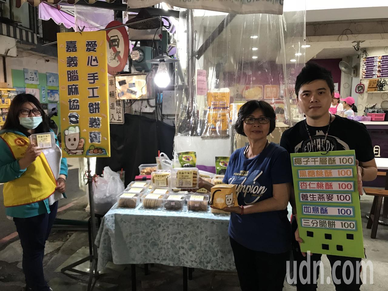 嘉義市腦麻協會理事長黃晨婷(右二)每天到嘉義市文化夜市擺攤,叫賣手工餅乾,增加協...
